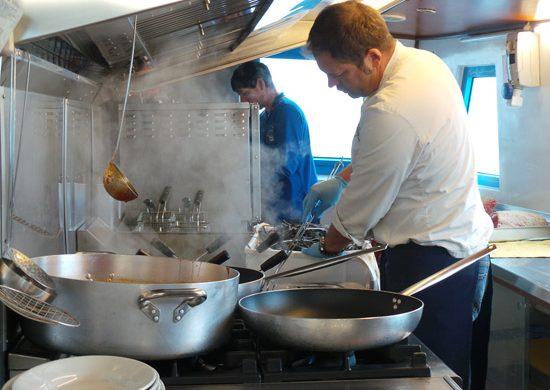 nico al lavoro nella cucina del battello santa maria nella laguna di Marano